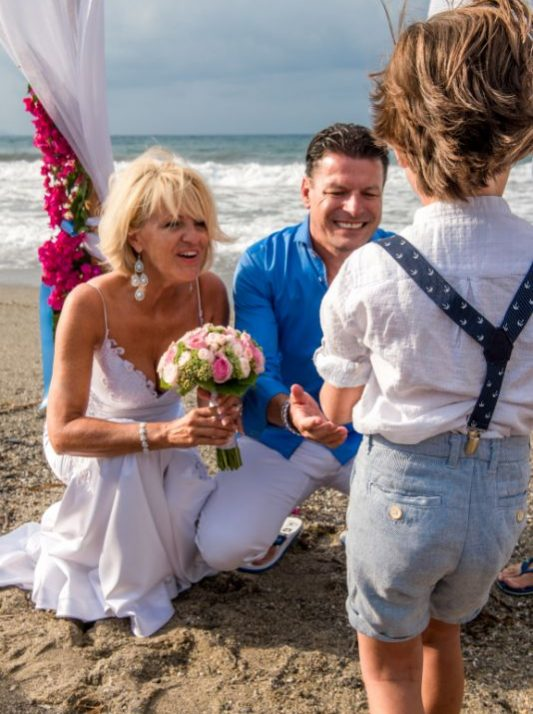 gamos-crete-weddings-couple-married-just-married-child-sand-laugh-happy-sea-beach-beach-front-bouquet-flowers-roses-pink-white-dress-bridal-blue-akky-roland