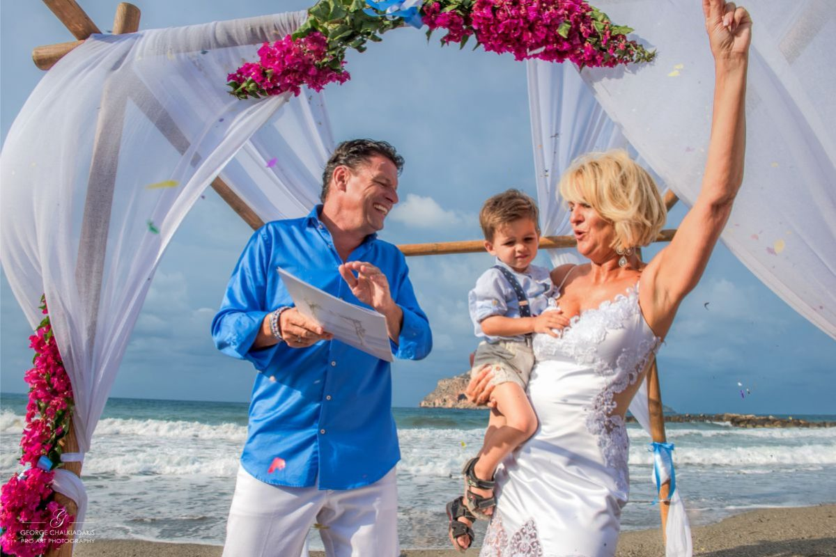 gamos-crete-weddings-happy-couple-people-child-vows-blonde-white-bridal-dress-trousers-shirt-sea-sea-front-man-woman-akky-roland