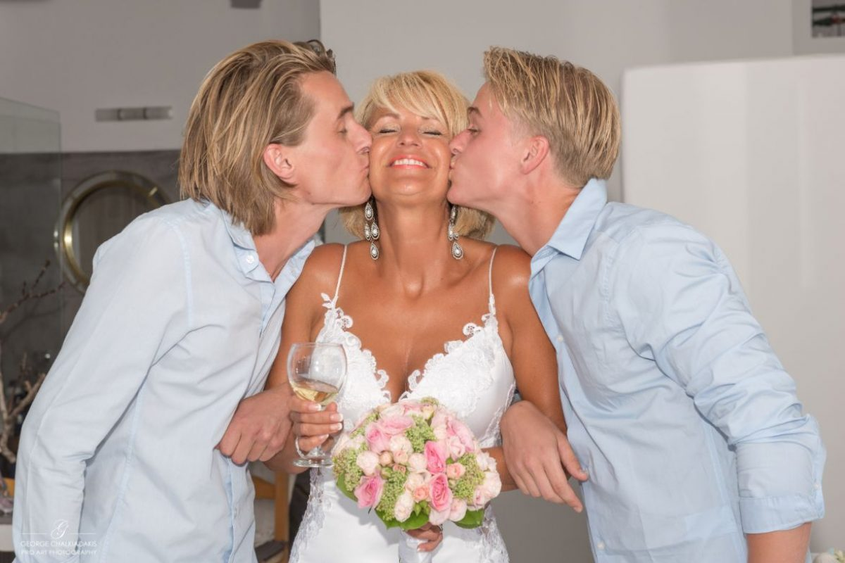 gamos-crete-weddings-kiss-bride-happy-people-bouquet-flowers-blonde-