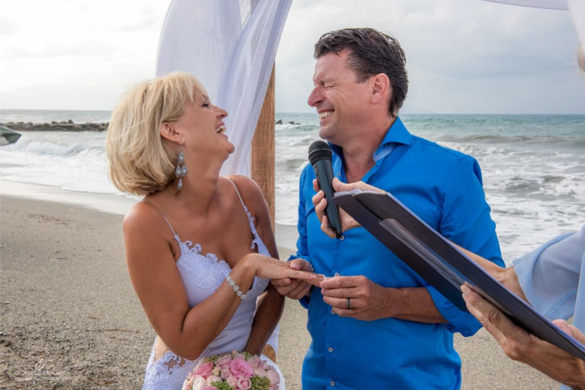 gamos-crete-weddings-vows-couple-married-just-married-blonde-darkhair-man-woman-white-bridal-dress-blue-shirt-microphone-beach-seafront-laughs-happy-people-akky-roland