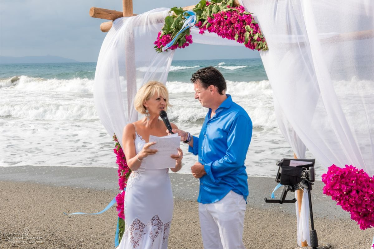 gamos-crete-weddings-vows-couple-sea-waves-seafront-sand-microphone-flowers-pink-white-bridal-dress-blue-shirt-just-married-akky-roland